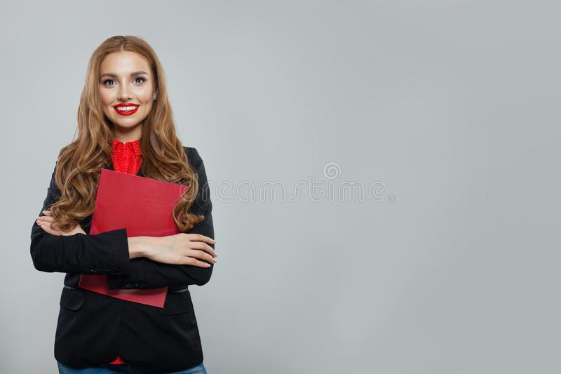 Happy business woman standing against white wall background. Businesswoman in black suit portrait stock image
