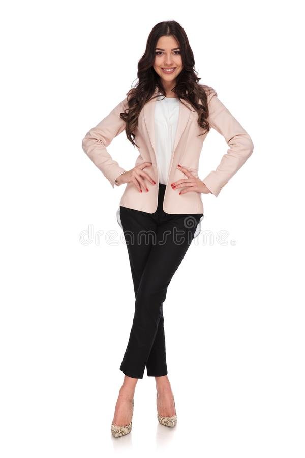 Happy business woman standing with legs crossed. And hands on waist on white background stock photography