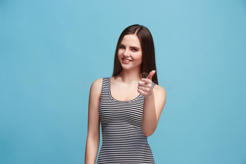 The happy business woman standing and smiling against blue background. royalty free stock photos
