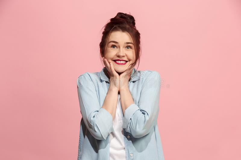 The happy business woman standing and smiling against pink background. royalty free stock images