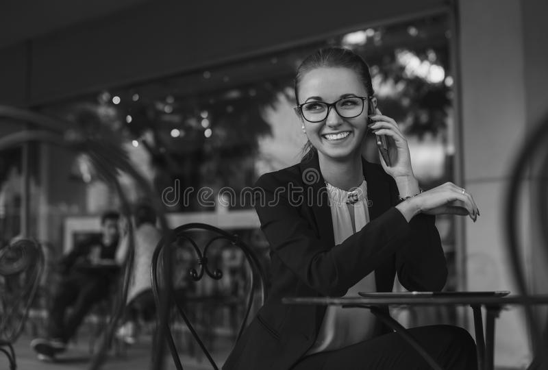 Business woman sitting in cafe and talking on the phone and smiling stock image