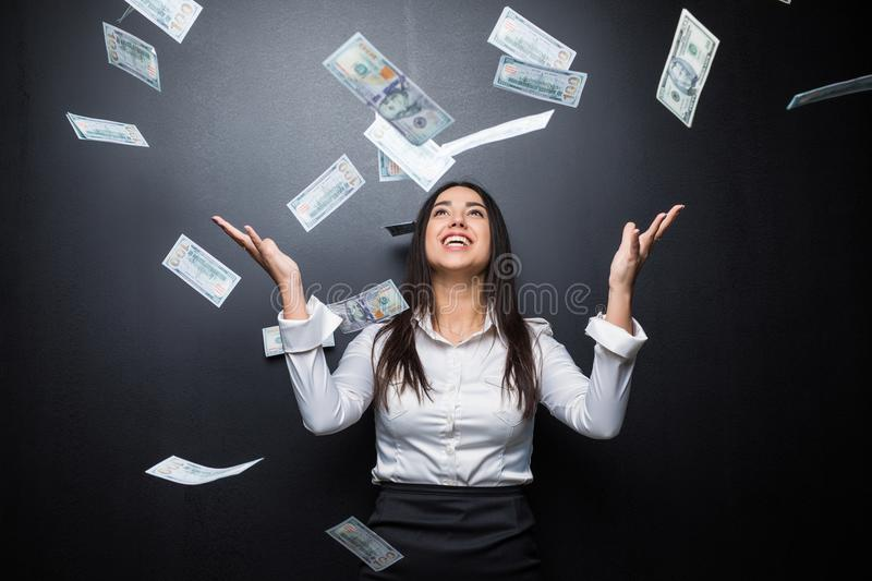 Happy business woman under a money rain made of dollars isolated on black royalty free stock photo