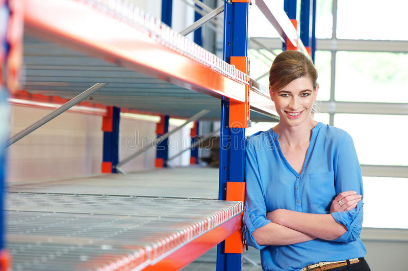 Happy business woman in warehouse stock photography