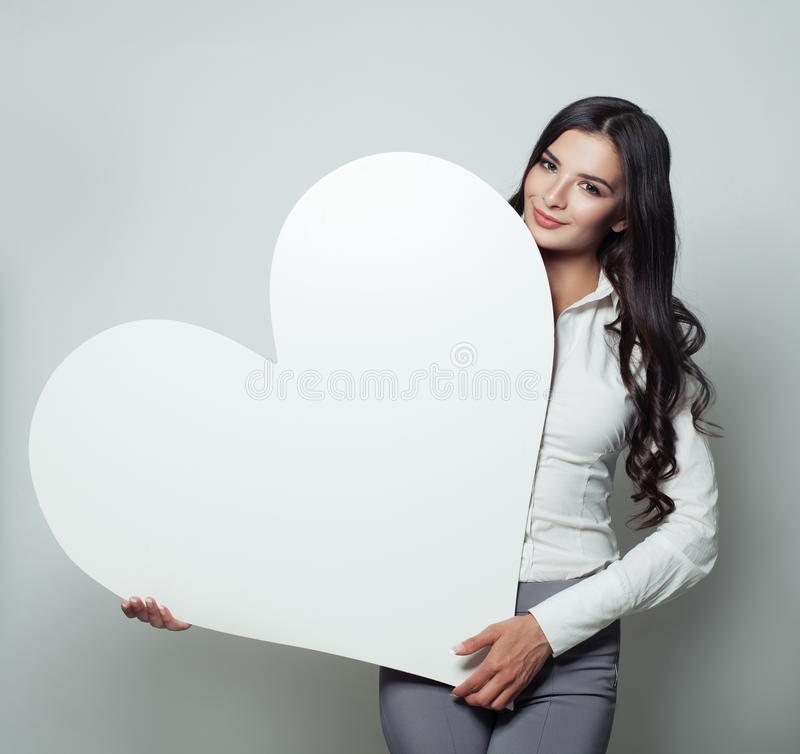 Happy business woman with white blank heart banner royalty free stock image