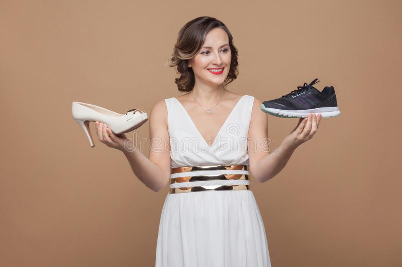 Happy business woman in white dress and holding sneakers and heel and toothy smiling at sporty sneakers. choosing comfortable royalty free stock photo