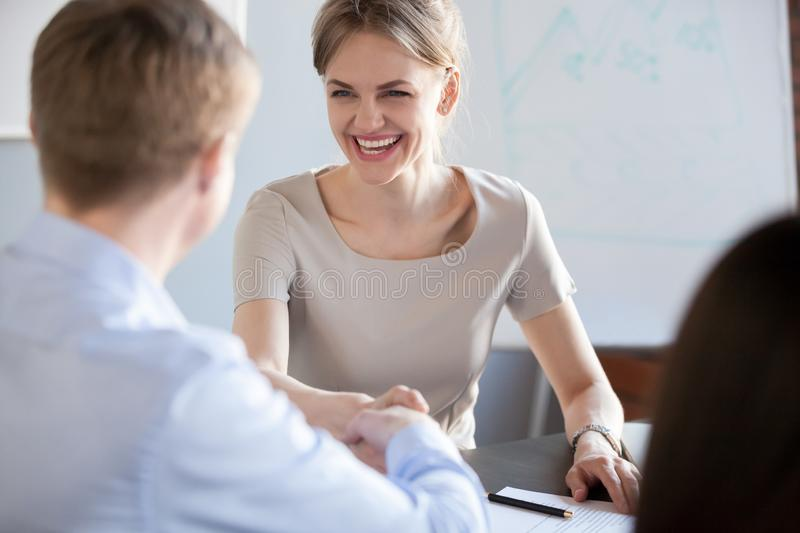 Happy business woman with wide smile handshaking new male partne. Happy business women with wide smile laughing handshaking new male partner after signing stock photos