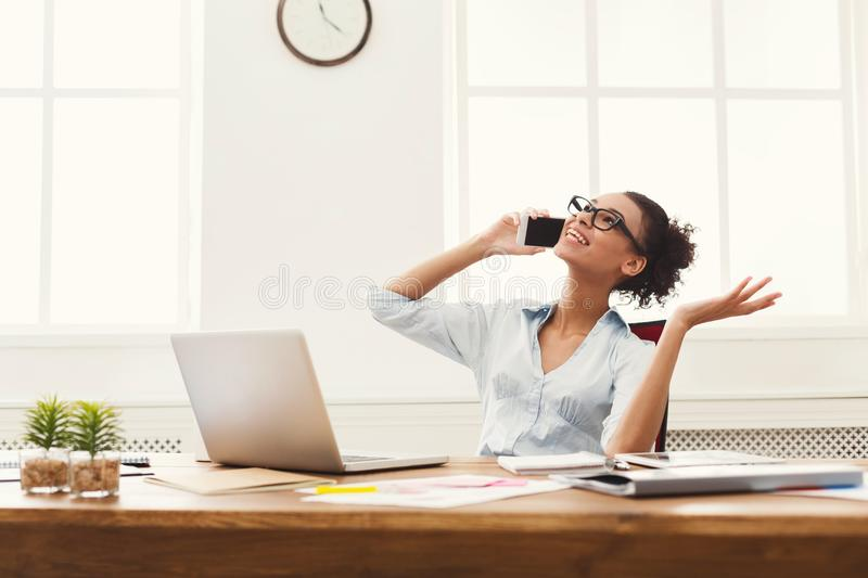 Happy business woman at work talking on phone. Happy smiling business woman at work talking on phone, sitting at her working place in office, copy space royalty free stock photo