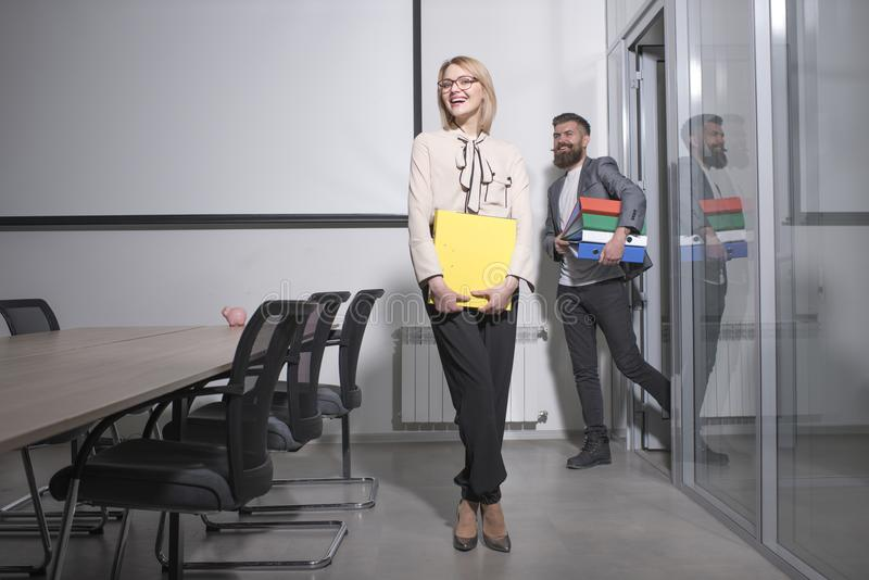 Happy business woman and man hold file folders. Sensual woman and bearded man smile in office. Paperwork and business. Happy business women and men hold file royalty free stock image