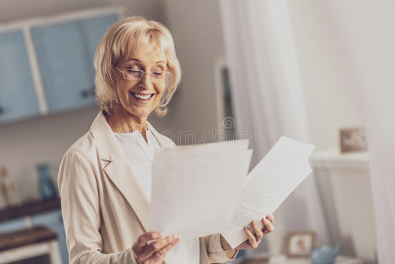 Happy businesslady being satisfied with results. Be positive. Beautiful blonde expressing positivity while comparing documents stock photo
