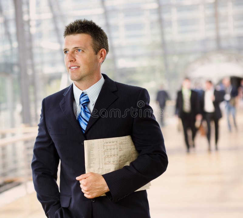 Happy businessman. Portrait of happy successful businessman holding newspaper, smiling royalty free stock photos