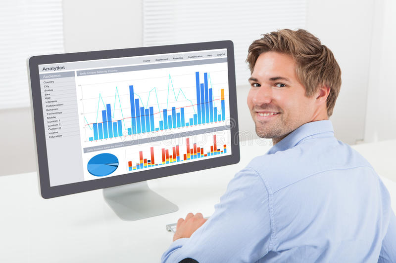 Happy businessman analyzing financial graphs on computer. Rear view portrait of happy businessman analyzing financial graphs on computer in office