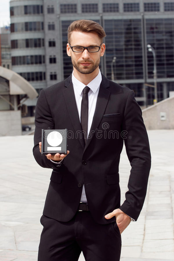 Happy Businessman with award. On urban background royalty free stock images