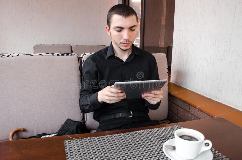Happy businessman in black suit use digital tablet at the cup of coffee in cafe. stock photos