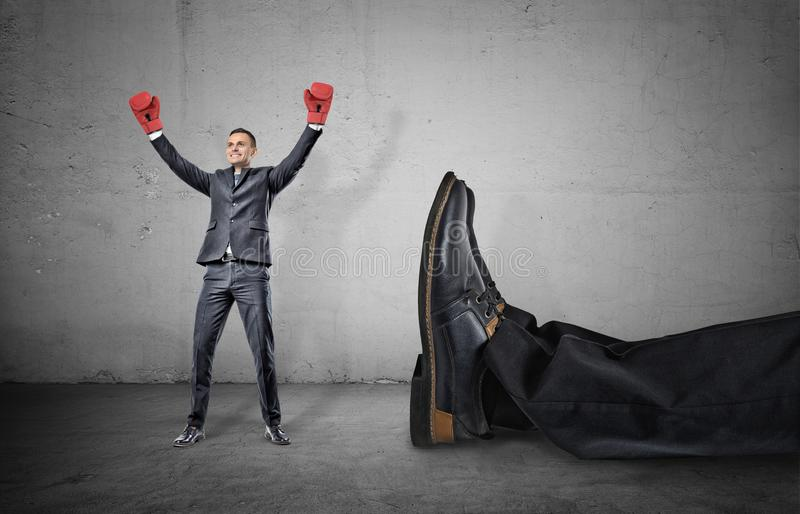 A happy businessman with boxing gloves on arms raised in victory stands near a giant male leg fallen down. stock photo
