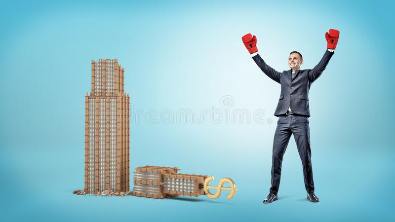 A happy businessman in boxing gloves stands near small broken business building with a golden dollar sign on its top. royalty free stock image