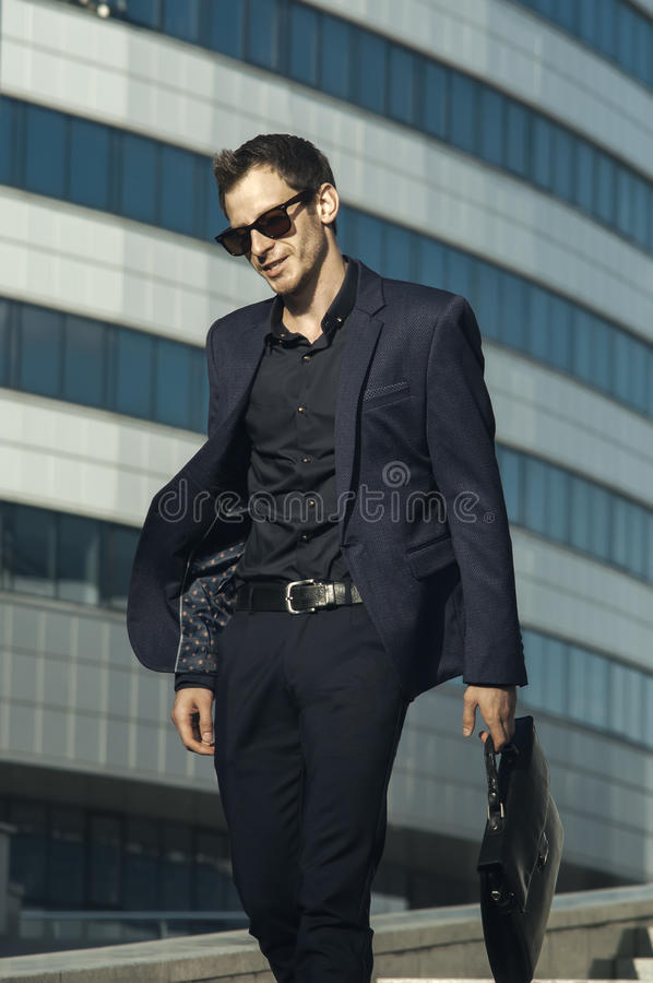 Happy businessman with briefcase in hand royalty free stock photo