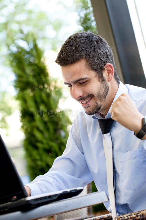 Happy businessman browsing on internet stock photography