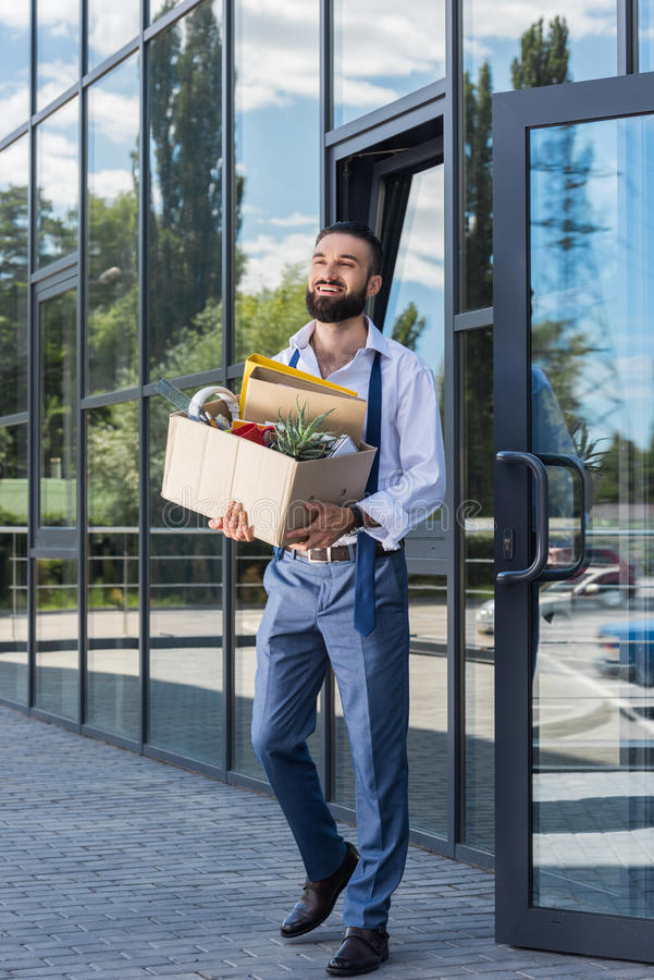 Happy businessman with cardboard box walking out office building royalty free stock photo