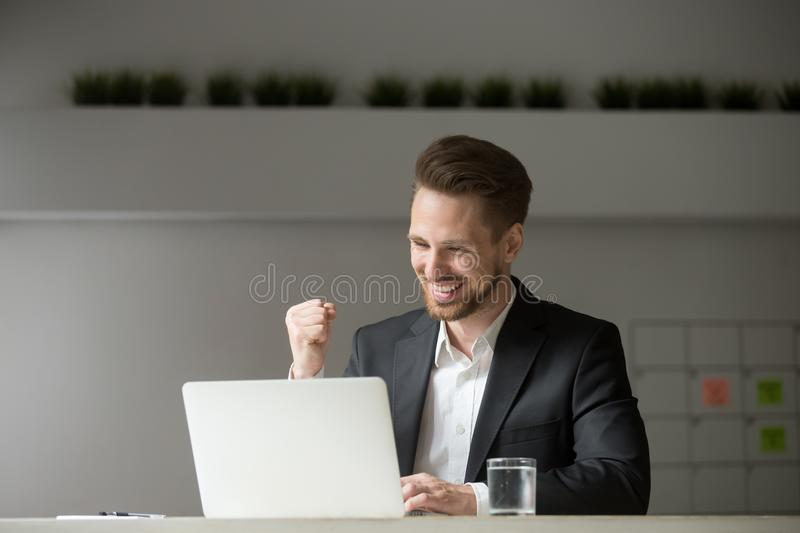 Happy businessman celebrating business success online win lookin stock photo