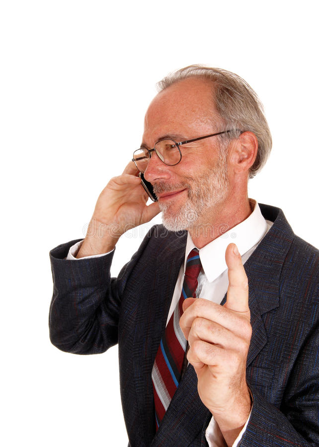 Happy businessman on cell phone. A middle age smiling business man talking on his cell phone, lifting up his finger, telling wait, isolated for white background royalty free stock photos