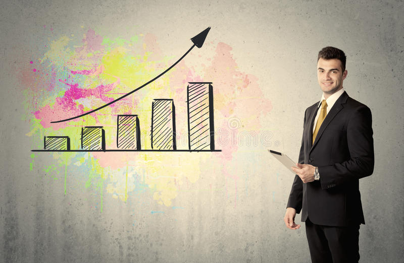 Happy businessman with colorful chart. An elegant businessman standing in front of a grey wall with colorful growing chart drawing concept royalty free stock image