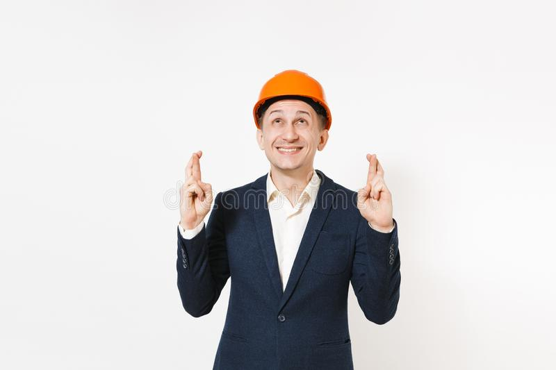 Happy businessman in dark suit, protective hardhat keeping fingers crossed and waiting for special moment isolated on stock image