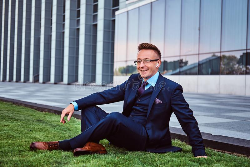 Happy businessman dressed in elegant suit sitting on a green lawn against cityscape background. royalty free stock image