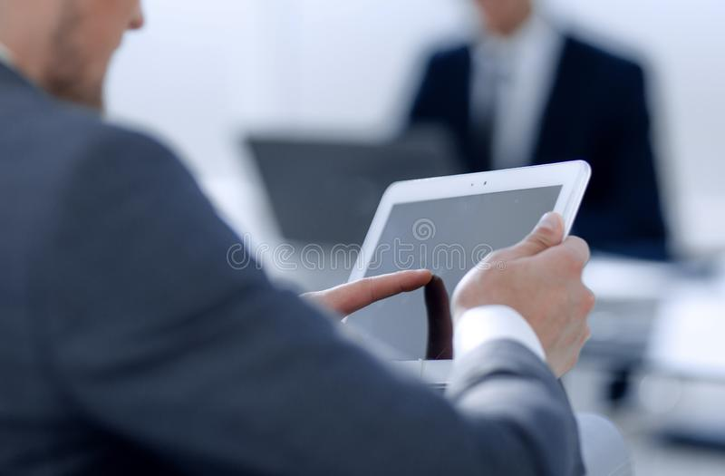 Businessman in suit in modern office using tablet royalty free stock photography