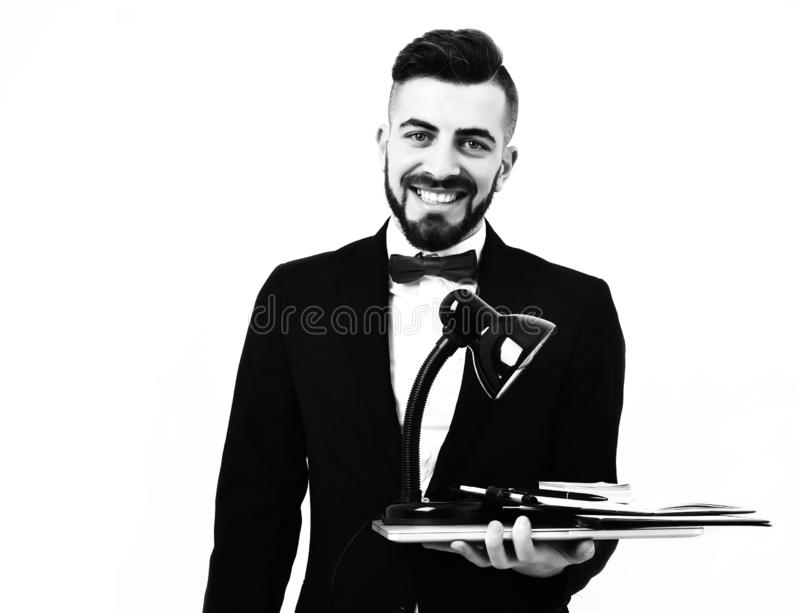 Happy businessman or executive director with beard and wide smile. Holds laptop with leather organizer and black table lamp, isolated on white background stock photography