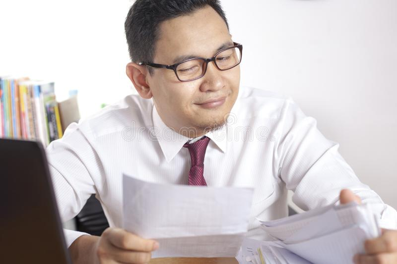 Happy Businessman Finding What He Looking For, Good News Concept. Portrait of happy Asian businessman finding what he looking for in archive at the office, happy royalty free stock image