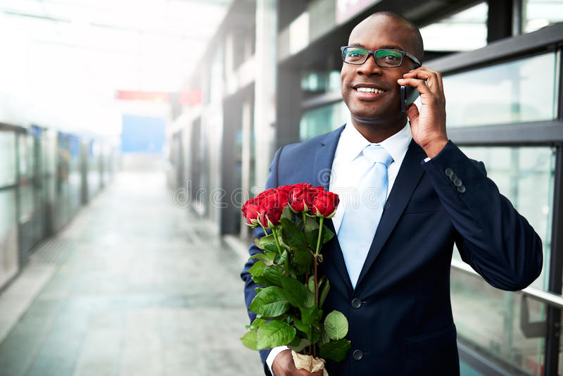 Happy Businessman with Flowers Calling on Phone. Happy Black American Businessman Holding Red Rose Flowers While Calling his Date on his Mobile Phone at the stock photo