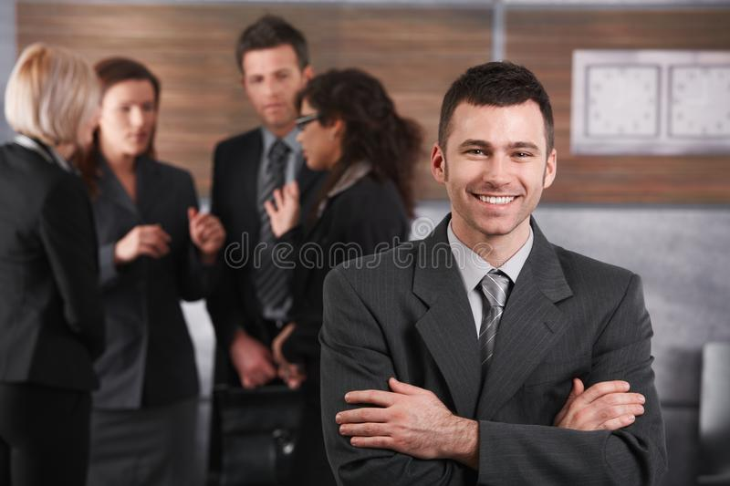 Happy businessman in front of team. Happy businessman standing in office in front of business team royalty free stock photos