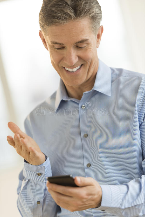 Download Happy Businessman Gesturing While Reading Text Message Stock Photo - Image: 32062402