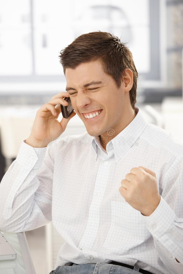 Happy businessman getting good news on phone stock images