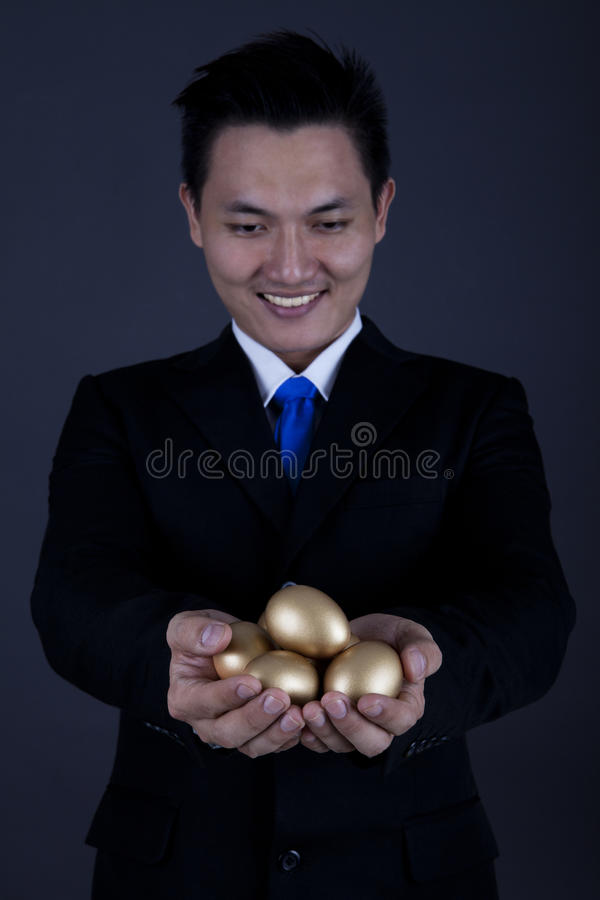 Happy Businessman With Golden Eggs Stock Photo
