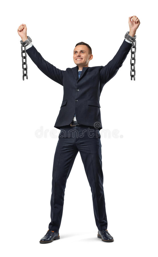 A happy businessman with hands raised up showing broken shackles on white background. Break free. Free business. Unlimited career royalty free stock photo