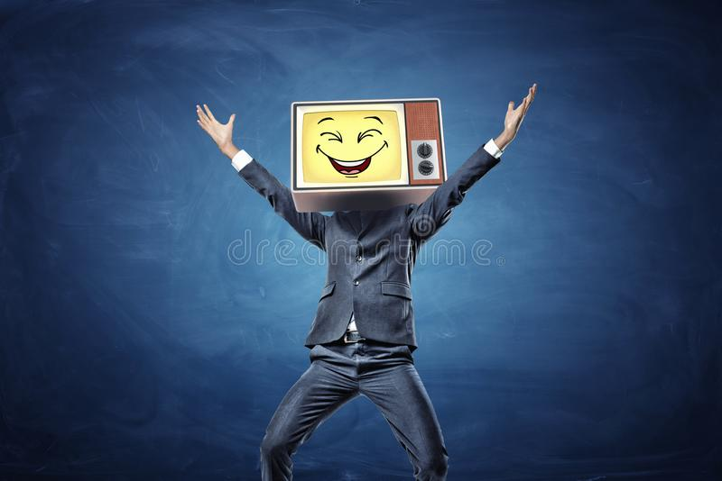 A happy businessman with hands raised in victory has a retro TV with a yellow smiley face instead of his head. Positive personality. Optimistic life. Happy and royalty free stock photography