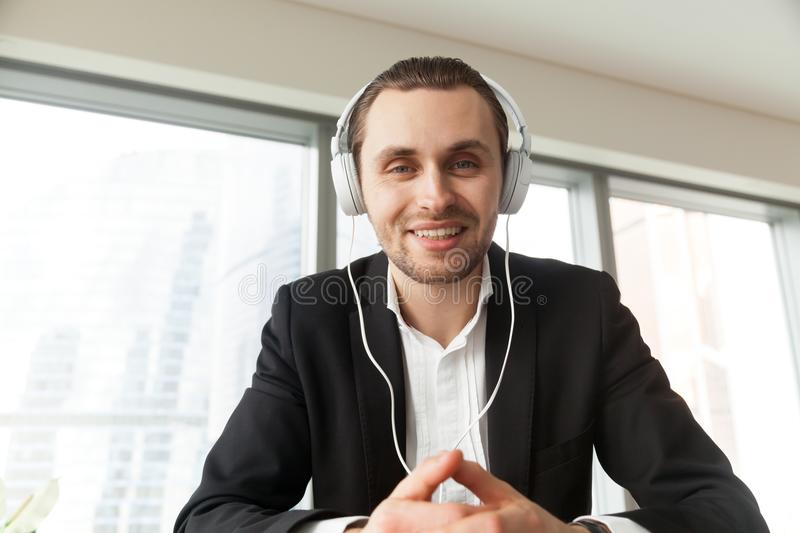 Smiling young businessman in headphones looking in camera. royalty free stock photography
