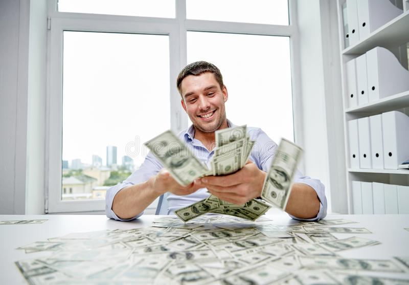 Happy businessman with heap of money in office stock photography
