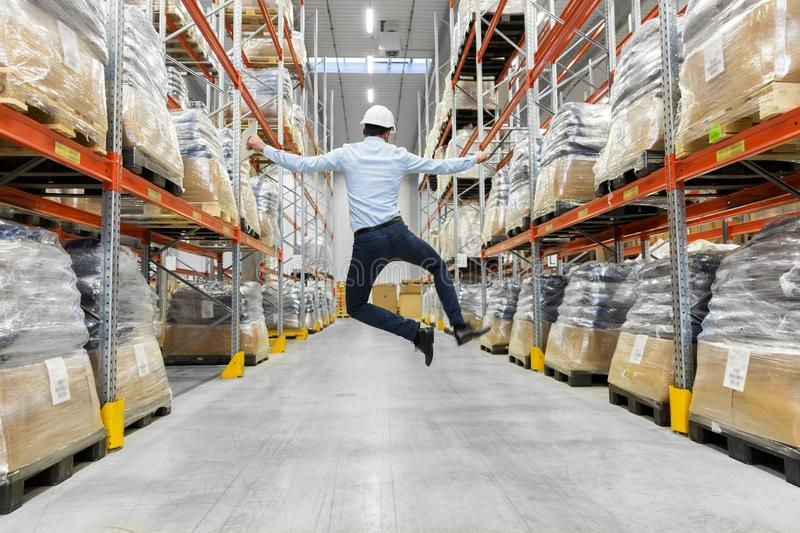 Happy businessman in helmet jumping at warehouse stock photos