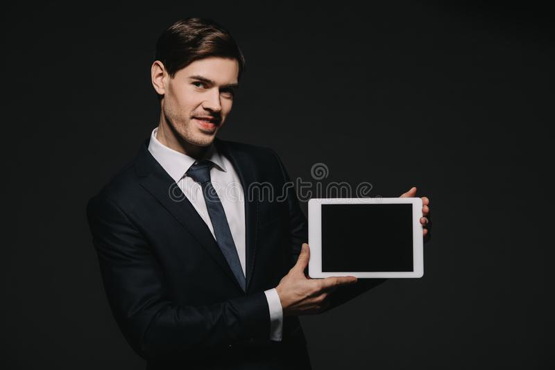 Happy businessman holding digital tablet with blank screen isolated stock image