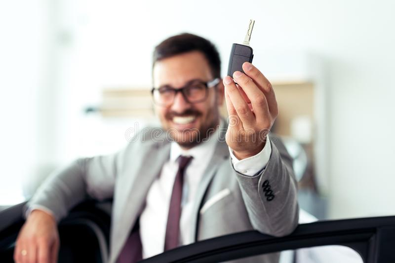 Happy businessman holding keys to her new car at the dealership. Young Happy businessman holding keys to her new car at the dealership royalty free stock images