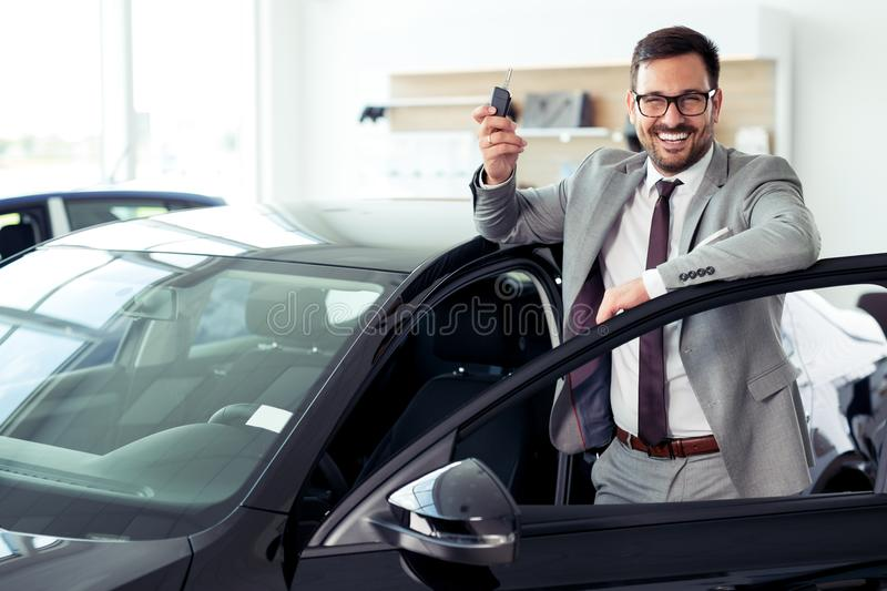 Happy businessman holding keys to her new car at the dealership. Young Happy businessman holding keys to her new car at the dealership stock photos