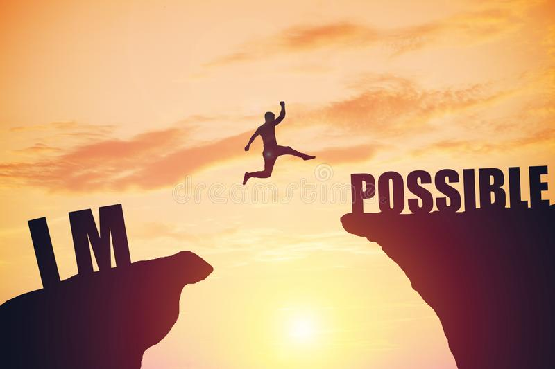 Happy businessman jumping between two rocks with words: IM POSSIBLE royalty free stock photo