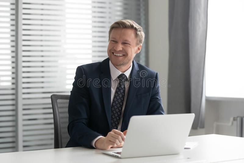 Happy businessman laughing, listening to joke, having fun at office. stock images