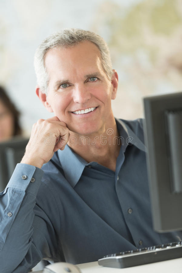 Happy Businessman Leaning At Computer Desk. Portrait of happy mature businessman leaning at computer desk in office royalty free stock photography