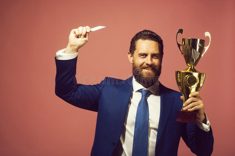 Happy businessman, man with golden champion cup and credit card. Business success and reward, victory and winning, tender and prize, happy businessman or man royalty free stock image