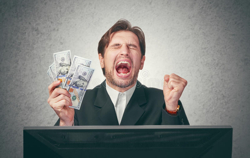Happy businessman with money in hand and computer royalty free stock images