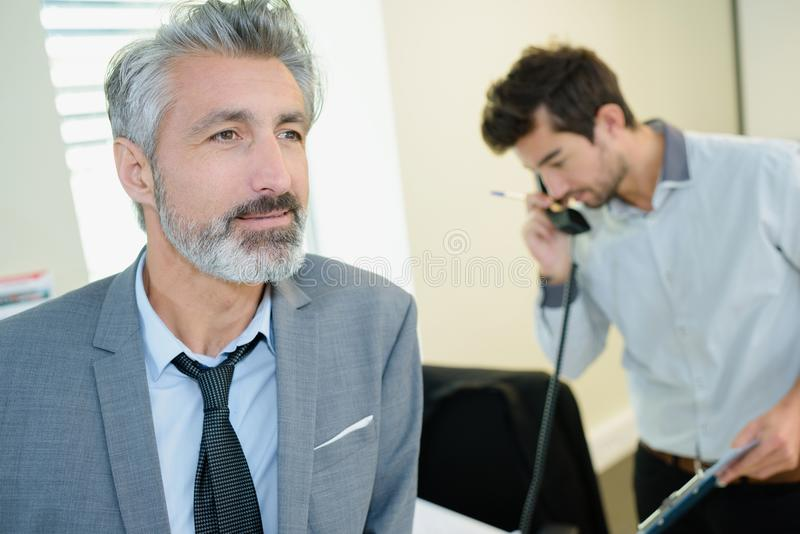 Happy businessman in office stock images