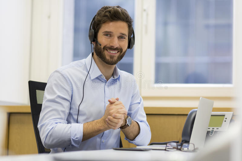 Happy Businessman in the office on the phone, headset, Skype royalty free stock photo